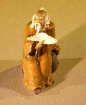 Miniature Figurine: Man Holding a Cup Sitting on a Rock
