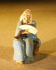 Miniature Figurine: Man Holding a Fan Sitting on a Rock